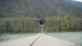 Girl traveler crossing the river on the suspension bridge, wood ferriage over the river. Woman hiker on suspension foot. Bridge over mountain river stock video footage