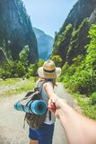 Girl traveler in a hat leads a guy`s hand against the background of the mountains Concept for travelers stock photos