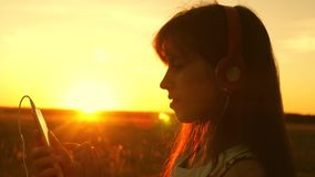 Girl traveler listening to music on smartphone in rays of a beautiful spring sunset. young girl with headphones and with stock footage