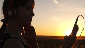 Girl traveler listening to music on smartphone in rays of a beautiful spring sunset. young girl with headphones and with stock video