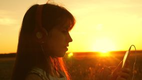 Girl traveler listening to music on smartphone in rays of a beautiful spring sunset. young girl with headphones and with. Girl traveler listening to music on stock video footage
