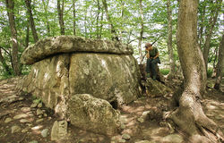 Girl traveler sits near ancient megalithic dolmen Royalty Free Stock Images
