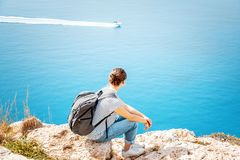 A girl traveler sits on a rock and admires the blue boundless se Stock Images