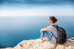 A girl traveler sits on a rock and admires the blue boundless se Stock Photo
