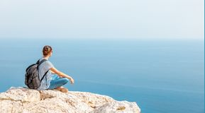 A girl traveler sits on a rock and admires the blue boundless se. A, freedom, travel, unity with nature Stock Image