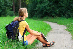 Girl traveler sitting on the grass Royalty Free Stock Image