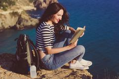 Girl traveler is sitting on mountain peak and reading book Royalty Free Stock Images