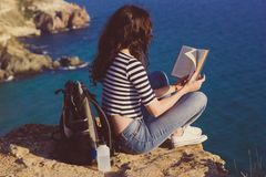 Girl traveler is sitting on mountain peak and reading book Stock Image