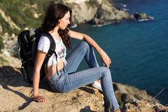 Girl traveler is sitting on rock over sea view Royalty Free Stock Photography