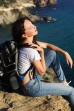 Girl traveler is sitting on rock over sea view Stock Photos