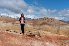 The girl traveler stands on a hill on the background of the orange-red mountains of the canyon stock photography