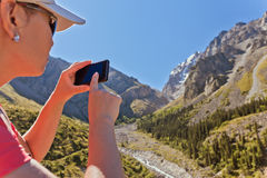 Girl-traveler using mobile in the mountains. Stock Image