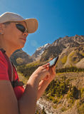 Girl-traveler using mobile in the mountains. Royalty Free Stock Photography