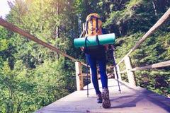 Girl traveler is walking along a wooden bridge stock photography