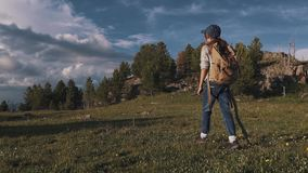 Girl traveler went Hiking in the mountains. a small child is on a mountain path. tourist with backpack and stick. slow. Girl traveler went Hiking in the stock footage