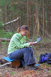 Girl-traveler in the woods reading a map Stock Photos