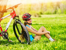 Girl traveling bicycle in summer park. Girl watch smart watch. Royalty Free Stock Image
