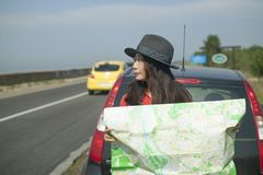 Traveling by car with a map on the road. Girl is traveling by car with a map on the road royalty free stock images