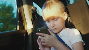 The girl is traveling in a car, playing on a smartphone. On the road with a child. 4K video stock footage