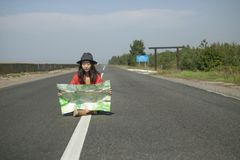 Traveling with a map on the road. Girl is traveling with a map on the road, conceptual photo stock images