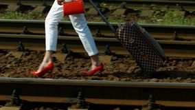 Girl traveling. Girl with a suitcase walking on the rails. Girl goes to study stock video footage