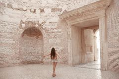 Girl traveller enjoying sightseeing interior door vestibule of t. He Diocletian`s palace in old city center of town Split, Croatia.  Ancient roman landmark. The Stock Images