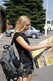 The girl-traveller with a map. The blonde girl-traveller with a map of the city and a backpack in the street Royalty Free Stock Photos