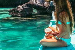 Girl travelling on the boat in Asia. Young girl relaxing on the boat, looking at clear sea water and eating coconut. Travelling tour in Asia: El Nido, Palawan Stock Photo