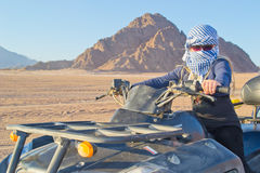Girl travels the desert. Girl travels on a quad in the desert. Evening soltse for katyvaetsya behind the mountains Stock Photos