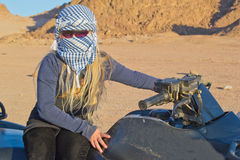 Girl travels the desert. Girl travels on a quad in the desert. Evening soltse for katyvaetsya behind the mountains Royalty Free Stock Photos