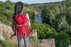 The girl travels.girl with a large backpack.tourist.red backpack stock image
