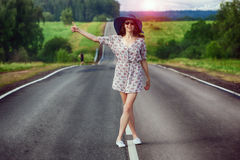 Girl travels on the highway hitchhiking Stock Images