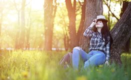 A girl travels the summer in the country. A girl in jeans and a hat travels the summer in the countryr Royalty Free Stock Photography