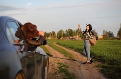 A girl travels the summer in the country. A girl in jeans and a hat travels the summer in the countryr Royalty Free Stock Image