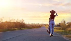 A girl travels the summer in the country. A girl in jeans and a hat travels the summer in the countryr Stock Image