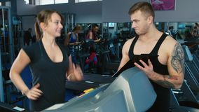 Girl on the treadmill. Attractive athletic woman training on a treadmill at the gym, the coach helps her stock video footage
