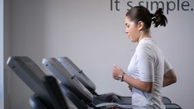The girl on the treadmill. First comes, accelerates, starts to run. 4K Slow Mo stock footage