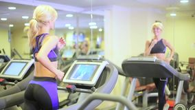 Girl on a treadmill in a fitness club.  stock video footage