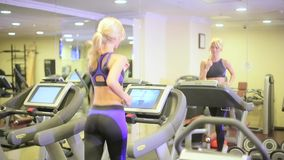 Girl on a treadmill in a fitness club stock video footage