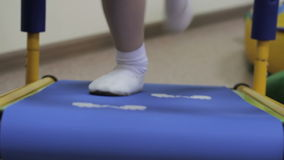 Girl on a treadmill. Little girl walks on a treadmill stock video footage