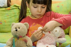 Girl treat her bear with bandage. Fun with doll-bear royalty free stock image