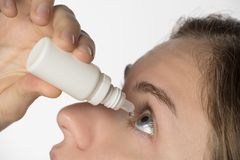 The girl bury drops in the eye with contact lenses from a white. The girl is treated and bury drops in the eye with contact lenses from a white bottle stock photos