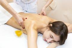 Girl treatment massage honey body wrap Stock Photos