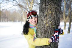 Girl and tree. Girl in a yellow jacket in the park in winter hiding behind a tree Stock Image