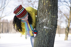 Girl and tree. Girl in a yellow jacket in the park in winter hiding behind a tree Royalty Free Stock Photography