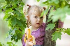 Girl on the tree with banana Stock Photo