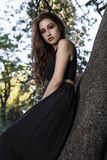 Girl in a tree. Beautiful Teenage Model Dressed in Fashionable S Stock Photography