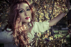Girl in a tree. Beautiful Teenage Model Dressed in Fashionable S Royalty Free Stock Photography