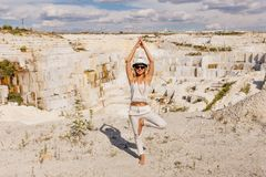 The girl in the tree pose, big white marble quarry, mining quarry Royalty Free Stock Image