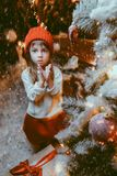 Girl at tree. Pretty child girl is sitting near the house decorated for Christmas with a gift. Time for miracles. Merry Christmas and Happy New Year stock photography